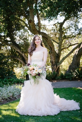 bride in blush ruffled mermaid dress, floral hairband, fresh-picked bouquet