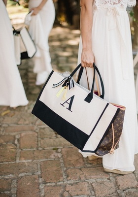 Bridesmaids in white dresses holding purses and monogram welcome tote bags embroidered with initials