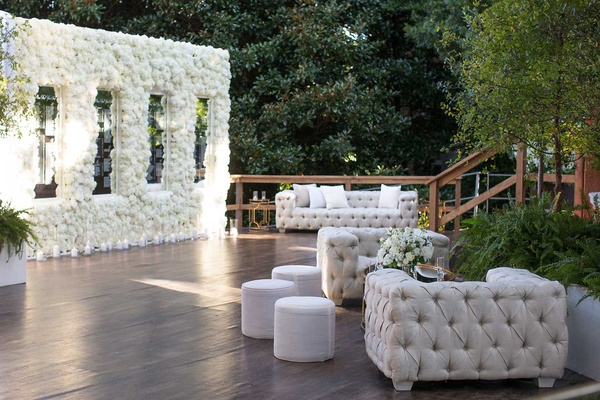 wedding cocktail hour lounge area tufted chesterfield sofa ottoman flower seating chart mirror names
