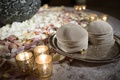 Suede kippa pile on silver platter next to candles