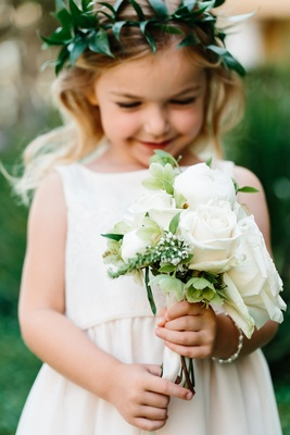Flower girl in white dress with green flower crown holding white rose bouquet of flowers