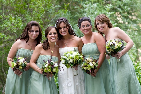 Bride in Claire Pettibone gown with bridesmaids in light green dresses