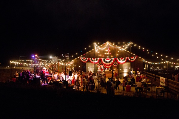 Wooden barn lit with string lights and decorated with red, white, and blue banners