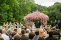 Wedding ceremony in countryside greenery pink and white little flowers on ceremony structure