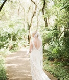 bride in alon livne lace dress with v-back and fingertip veil