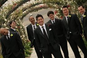 Groom with six groomsmen under flower archways