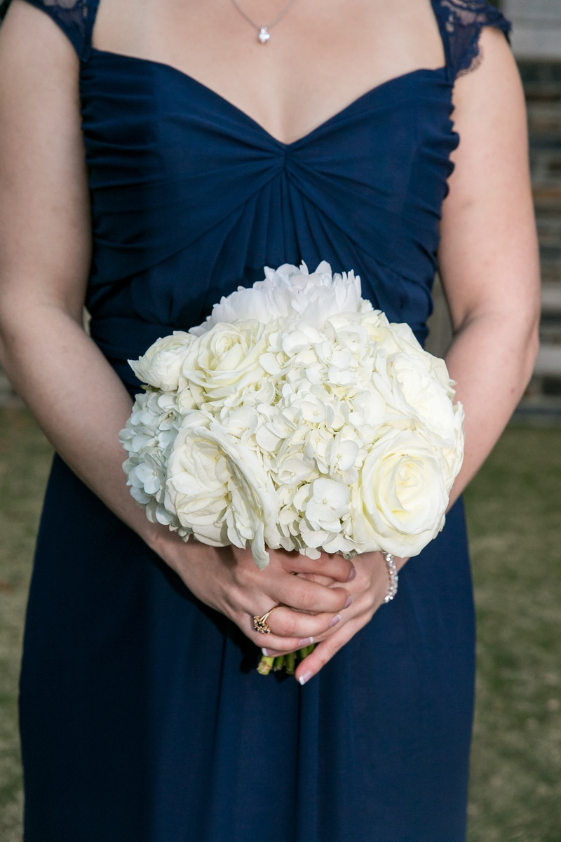 Bridesmaid in blue dress holding white rose and white hydrangea bouquet
