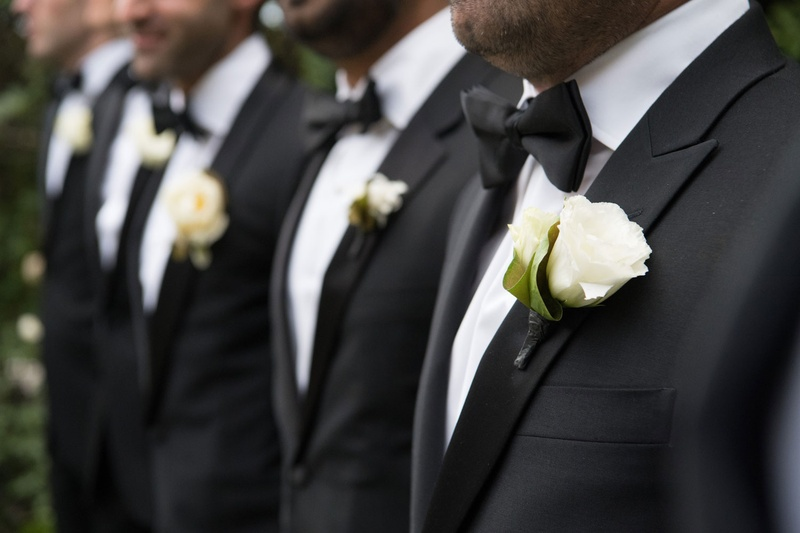 Line of groomsmen in tuxedos wearing matching bow ties and flower boutonniere rose style