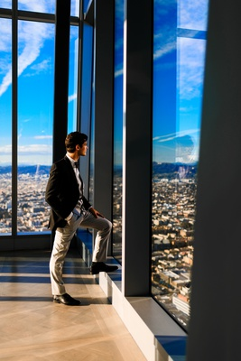 groom in mismatched suit, grey slacks, black jacket, looks out high rise window in downtown la