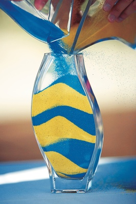 yellow and blue sand layered in glass jar for ceremony