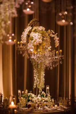 wedding reception tall centerpiece chandelier white orchid and roses tulip flowers at base candles