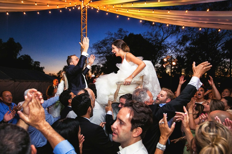 a newlywed couple lifted up in two different chairs by the guests at their reception