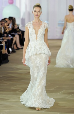 Sleeveless Alençon lace sheath gown with plunging neckline, cap sleeves, and detachable peplum train