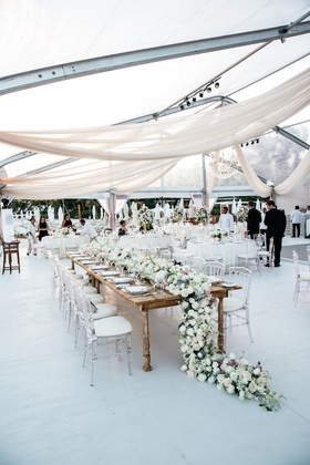 Beach wedding with a clear tent, draping and head table with runner of white, pink flowers, greenery