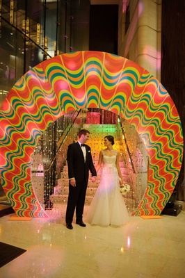 Bride in Monique Lhuillier wedding dress and groom in tuxedo at Trump Hotel Chicago fun wheel entry