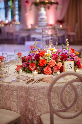 Rosette pattern linens white chairs gold charger plates pink orange red flowers around hurricane