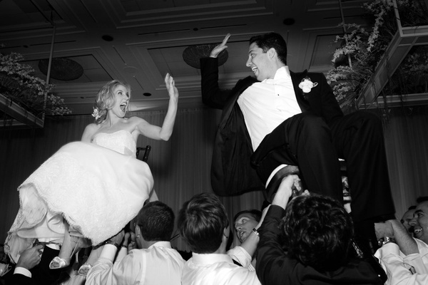 Black and white photo of bride and groom hora dance