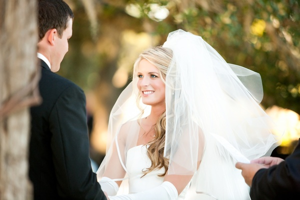 Bride at ceremony with white satin-trim veil