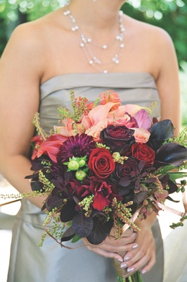 Bridesmaids carrying dark colored flowers