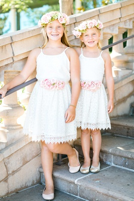 Two flower girls in matching white lace dresses with pink rose belt flower crowns and flats