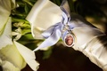 Golden charm with rhinestones around photo of mother of the bride tied with ribbon to bridal bouquet