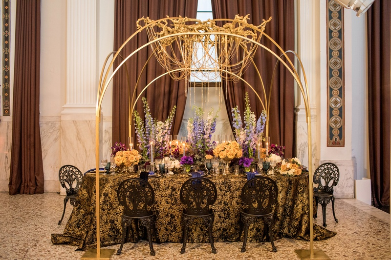 wedding styled shoot, gold chain chandelier, blue delphiniums, black and gold
