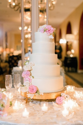 White wedding cake with beaded borders, white & pink garden roses on gold stand, votive candles