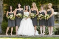 Bride with bridesmaids in short gray dresses and fern bouquets
