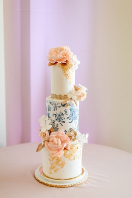 narrow, three-tier cake with blue floral tier and peach sugar flowers.