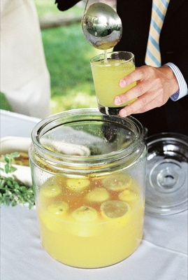 Big jar filled with lemon halves and yellow drink