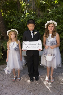 Flower girls in silver with suited ring bearer with funny sign