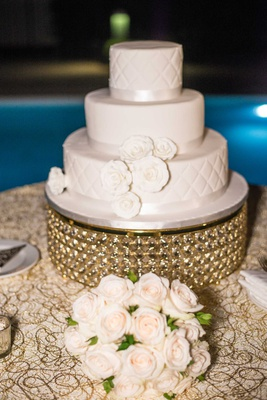 wedding cake on gold stand white sugar flowers ribbon quilted layer tier