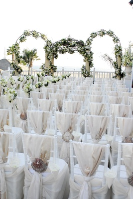 white chairs covered in fabric and large seashells
