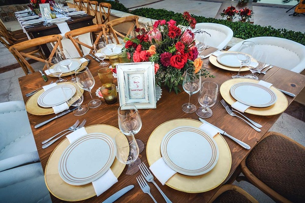 small square wooden table with gold charger plates and small centerpieces red pink orange greenery