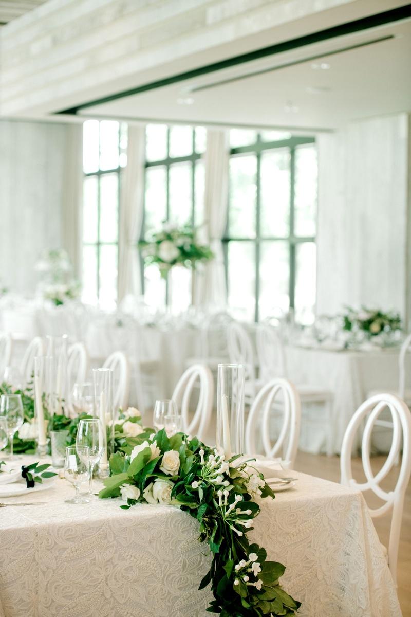 wedding reception long table white linen greenery white rose flower centerpiece runner taper candles