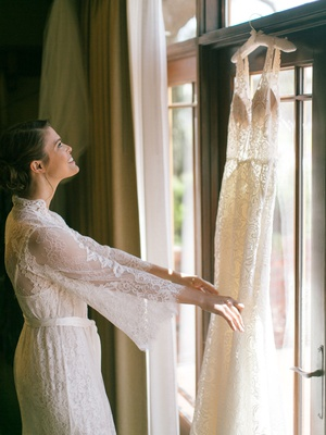 bride in lace robe looking at wedding dress hanging in window