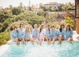 Bride in white shirt monogram and bridesmaids in blue shirts monograms sunglasses with feet in pool