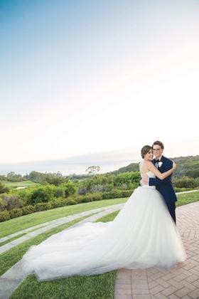bride in vera wang ball gown hugging groom in navy blue tuxedo on lawn overlooking ocean