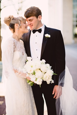 bride in monique lhuillier, groom in jos a bank, closed eyes smile during first look