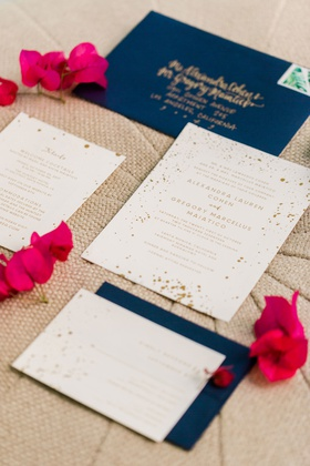 wedding invitation gold and white splatter confetti theme with navy blue envelope gold calligraphy