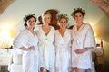 bride in white lace-trimmed robe, bridesmaids in light floral robes and flower crowns