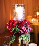 Gold candlestick with votive, red roses, greenery on reception table