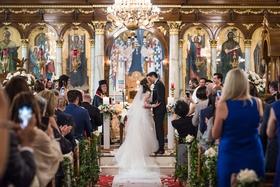 wedding ceremony greek orthodox cathedral gold foil chandelier greenery church pews