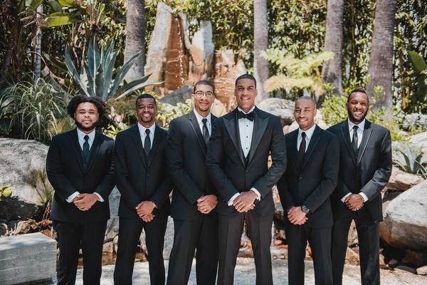 groom in custom tuxedo and textured jacket, groomsmen in three-piece suits