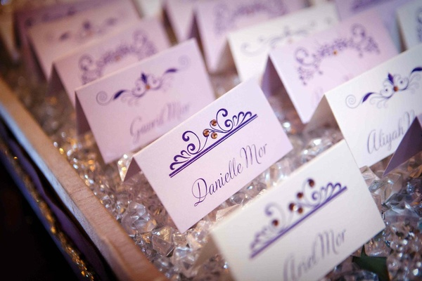 White seating cards with purple script and rhinestones
