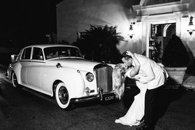 black and white photo of bride and groom kissing in front of rolls royce classic car wedding