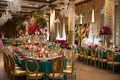 turquoise pink gold tablescape area varying levels of floral arrangements candles gold chairs