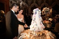 Bride and groom cut into layered wedding cake with multicolor flowers