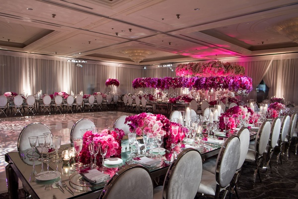 Bright pink flower centerpieces on mirror table with velvet grey and chrome chairs round oval backs