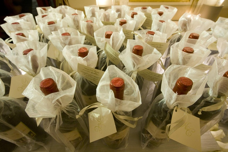 Wedding favors of wine bottles in sheer white bags